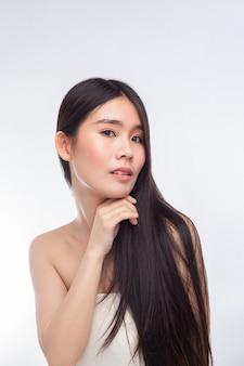 白いストラップレスのドレスとあごに触れる手を着ているアジアの女性。