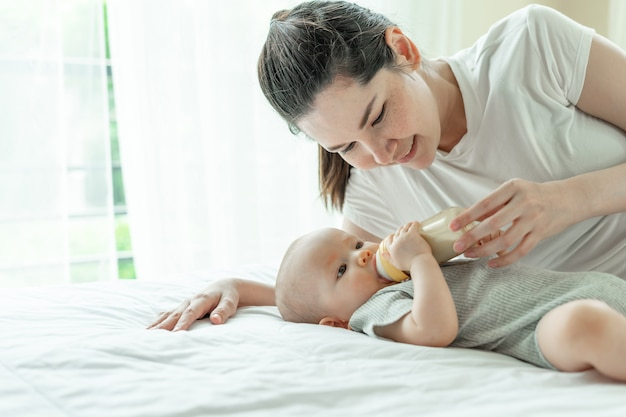 Малыш пьет молоко из бутылочки с мамой рядом с ним
