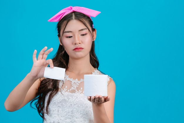 Девушка в белой пижаме, держа в руке рулонной бумаги на синий.