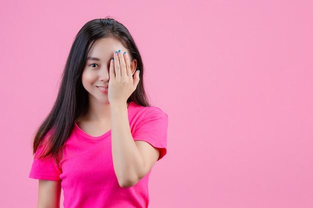 白いアジアの女性が左手をピンクの片方の目につけます。
