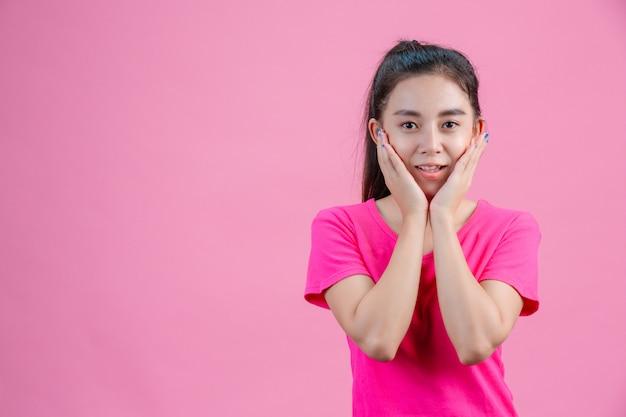 アジアの白人女性はピンクのシャツを着ています。ピンクの顔を両手で持って。