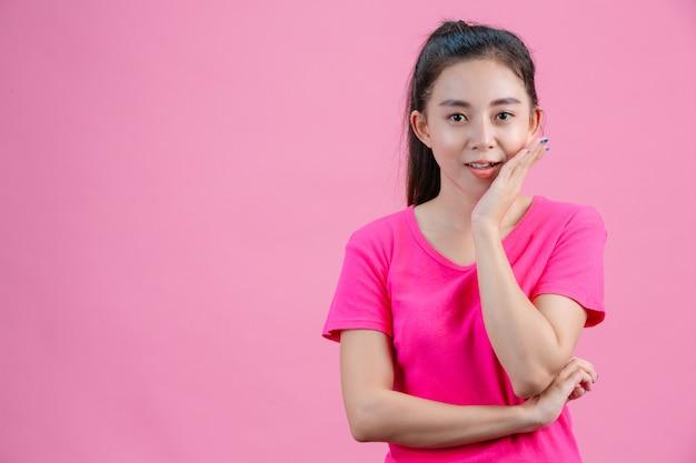 アジアの白人女性はピンクのシャツを着ています。ピンクの顔に彼の左手を置いてください。