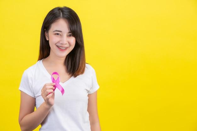 Рак молочной железы, женщина в белой футболке с атласной розовой лентой на груди, символ осведомленности о раке молочной железы