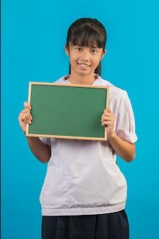 Азиатский студент при длинная девушка волос держа зеленую доску на сини.