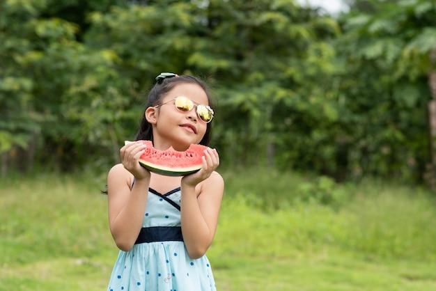 アジアの女の子はスイカを保持します