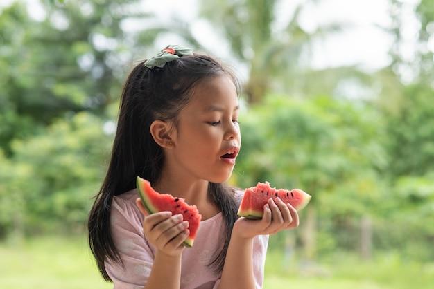 スイカを食べるアジアの女の子