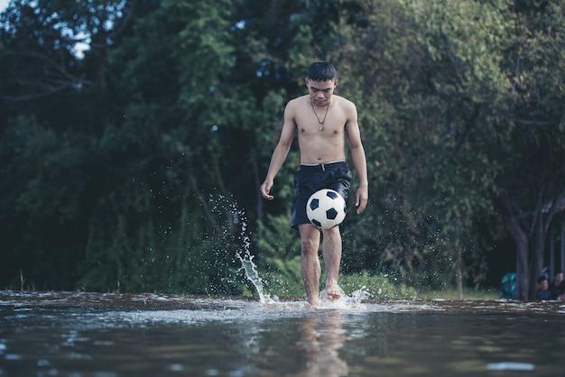 アジアの少年は川でサッカーボールを蹴る