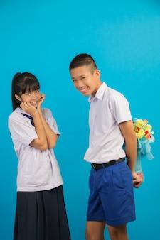 Молодые азиатские студенты и азиатские студенты стоят вместе на синем.
