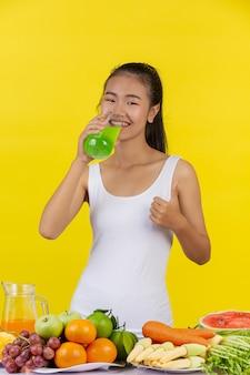 Азиатка пьет яблочный сок, а на столе много фруктов.