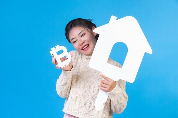 美しい女性は、家のシンボルとバーツを青にした新しい長袖の白いシャツを着ます。ハウス取引。