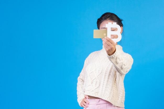 Красивые женщины носят новый белый с длинными рукавами ковер, держа символ тайского бата и золотую кредитную карту на синем. торговая