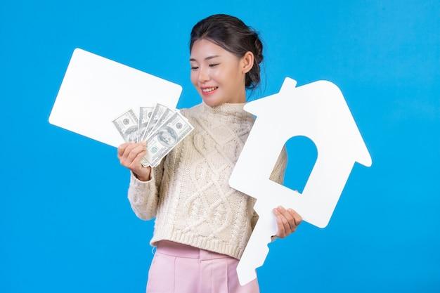 家のシンボルを保持する新しい長袖の白いカーペットを着て美しい女性。白いプラークと青のドル札。貿易 。
