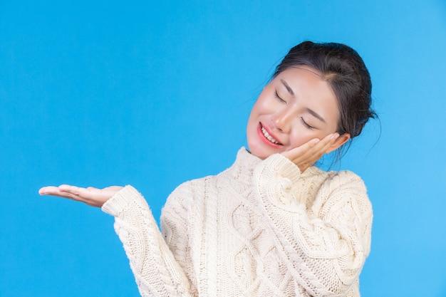 青のジェスチャーを示す新しい長袖の白いカーペットを着て美しい女性。貿易 。