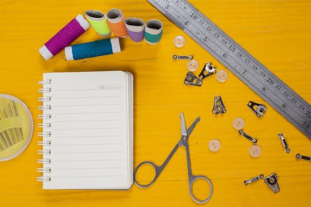 黄色の木の床に置かれた裁縫キット、針、糸、針。