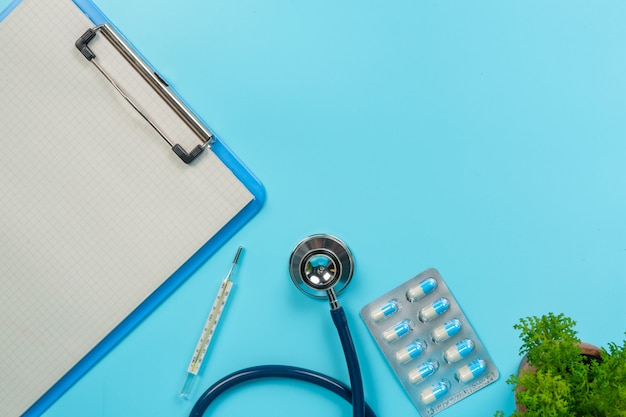 青の執筆板および医者用具と並んで置かれる薬、医薬品の。