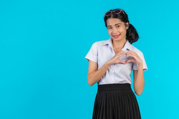 アジアの女子学生が青のさまざまな位置でポーズします。
