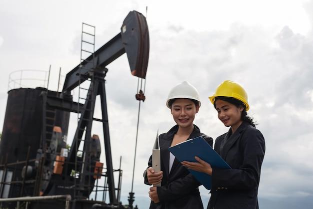 Две женщины-инженеры стоят рядом с работающими масляными насосами с белым небом.