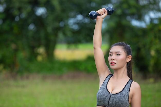 公園でダンベルを持ち上げて上腕を行使する美しい女性。