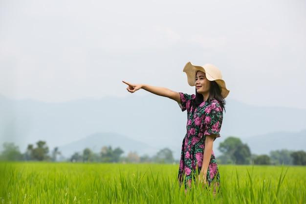 Девушка в цветочном платье стоит на лугу