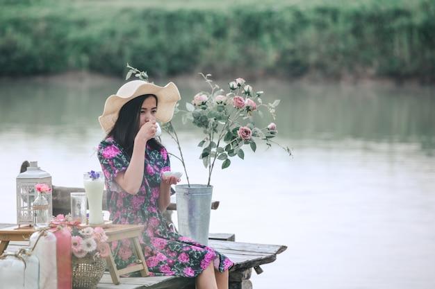 Девушка в цветочном платье сидит на набережной