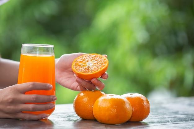 オレンジ色の果物を手に持っている人