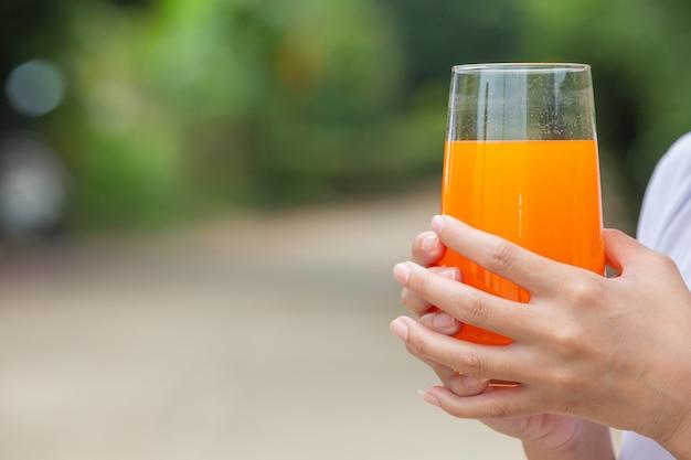 Красивая женщина в белой футболке держит стакан апельсинового сока