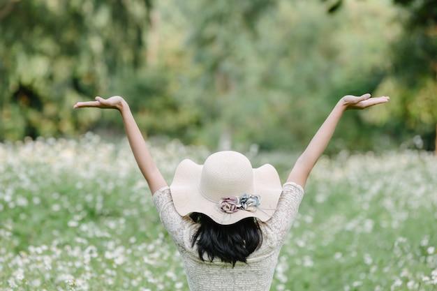 花のフィールドに立っている、かわいい白いドレスを着ている美しい女性