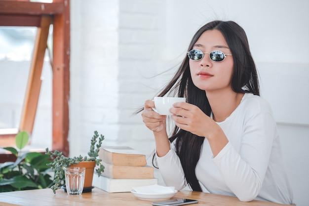 コーヒーショップに座っている長袖の白いシャツを着ている美しい女性