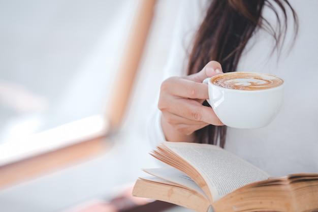 Красивая женщина в белой рубашке с длинными рукавами сидит в кафе