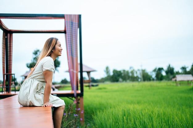 Женщина сидит и отдыхает на лесном мосту с опущенными ногами