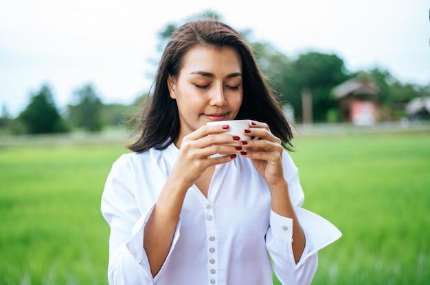 Женщина стояла счастливо пить кофе на лугу