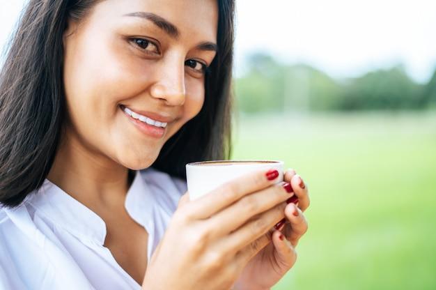 女性は牧草地で喜んでコーヒーを飲んで立っていた