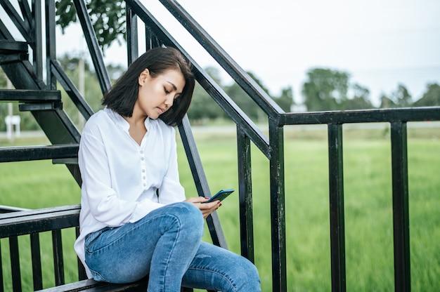 スマートフォンを見て、ストレスを抱えている梯子の上に座っている女性