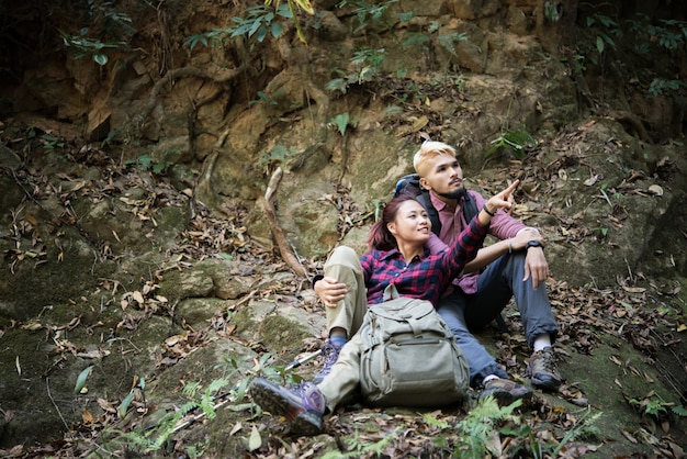 若い観光客のカップルは、滝の近くで休憩を取って、森林をハイキングしながら、観光スポットを探しています。旅行のコンセプト。