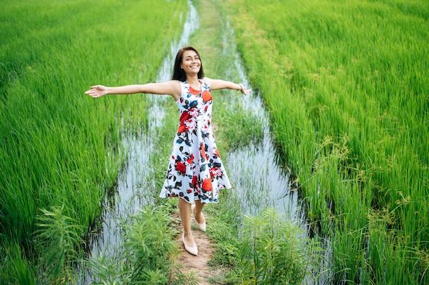 美しい女性は牧草地で楽しく歩きます
