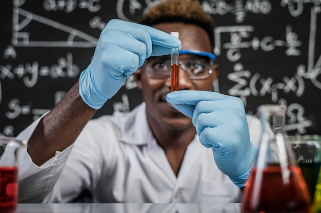 Ученые смотрят на оранжевые химикаты в стекле в лаборатории
