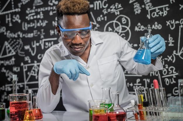 科学者はスカイブルーの化学物質を持ち、実験室でガラス中の化学物質を見る