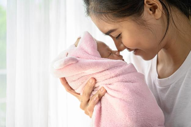Новорожденный ребенок спит на руках у матери и нос столкнулся