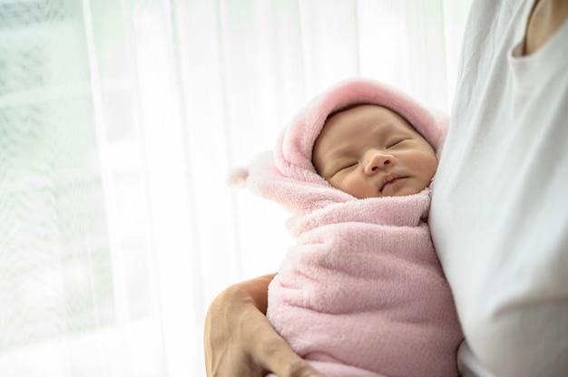 Новорожденный ребенок спит в объятиях матери