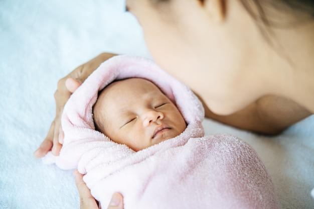 Новорожденный ребенок спит на руках у матери