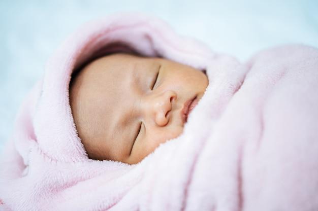 Новорожденный ребенок спит на мягком розовом одеяле