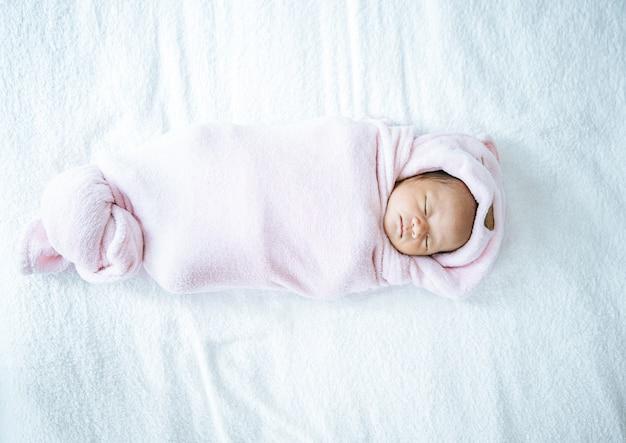 柔らかいピンクの毛布で寝ている生まれたばかりの赤ちゃん