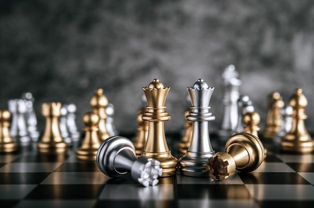ビジネスメタファーリーダーシップコンセプトのチェスボードゲームで金と銀のチェス