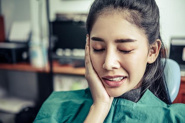 その女性は歯痛で、頬に手を触れていました。