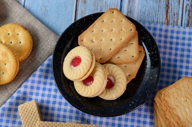 Укладывают много видов печенья на тарелку и ставят на деревянный стол.