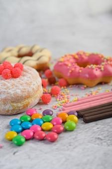 Пончики посыпать сахарной пудрой и конфеты на белой поверхности.