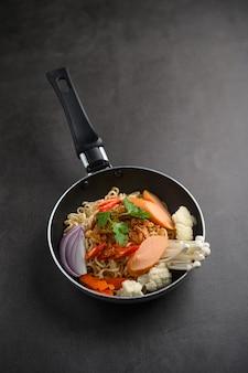 黒のセメントの床にフライパンで麺のある静物。
