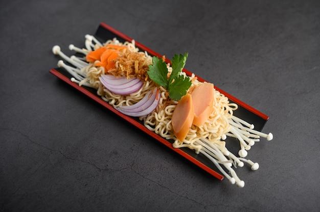 黒いセメント表面に食材を使った木製のトレイでスパイシーな麺。