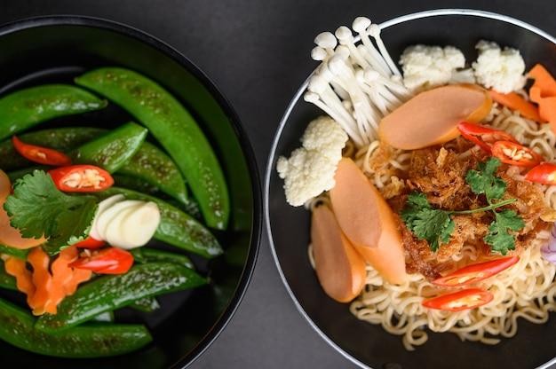フライパンでエンドウ豆を炒め、ボウルに黒セメントの表面に食材を使ったスパイシーな麺。
