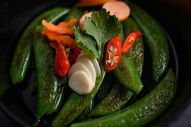 黒いセメント表面のフライパンで豆を炒めます。
